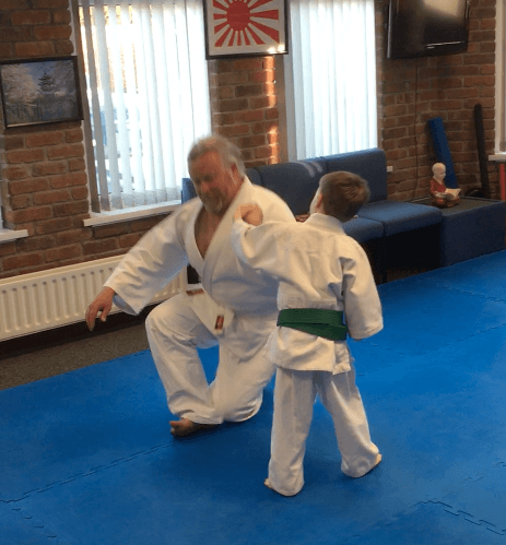 Young Aikido boy dropping an older man in the dojo. Martin Acton's Aikido Institute