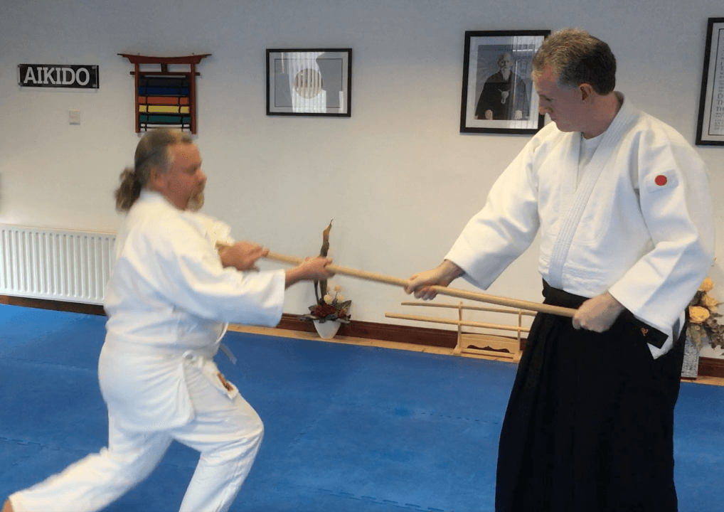 Aikido student throwing a person using a staff.