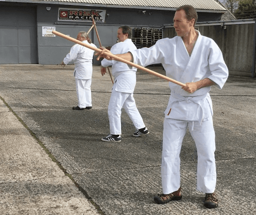 There Aikido students practicing the jo forms outside.