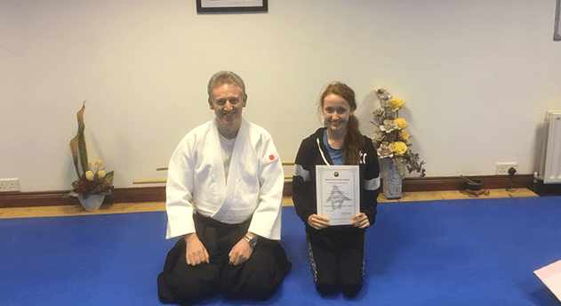 learning Japanese. Young Girl receiving her certificate for graduating 6 week Japanese language course. Martin Acton's Aikido Institute