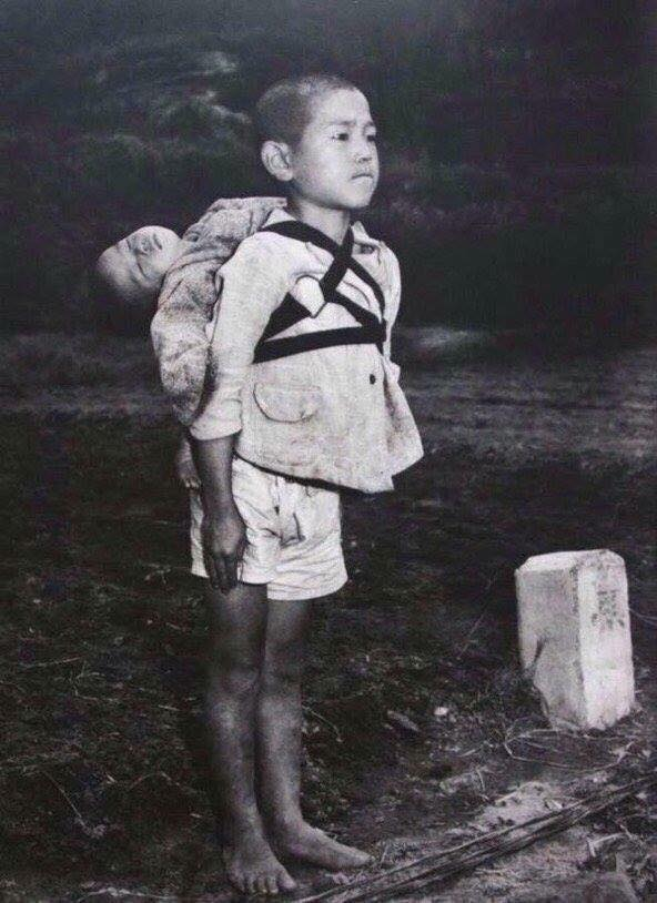This is a photo of a young Japanese boy with his little sister on his back after the Nagasaki explosion in 1945.  War is wrong!
