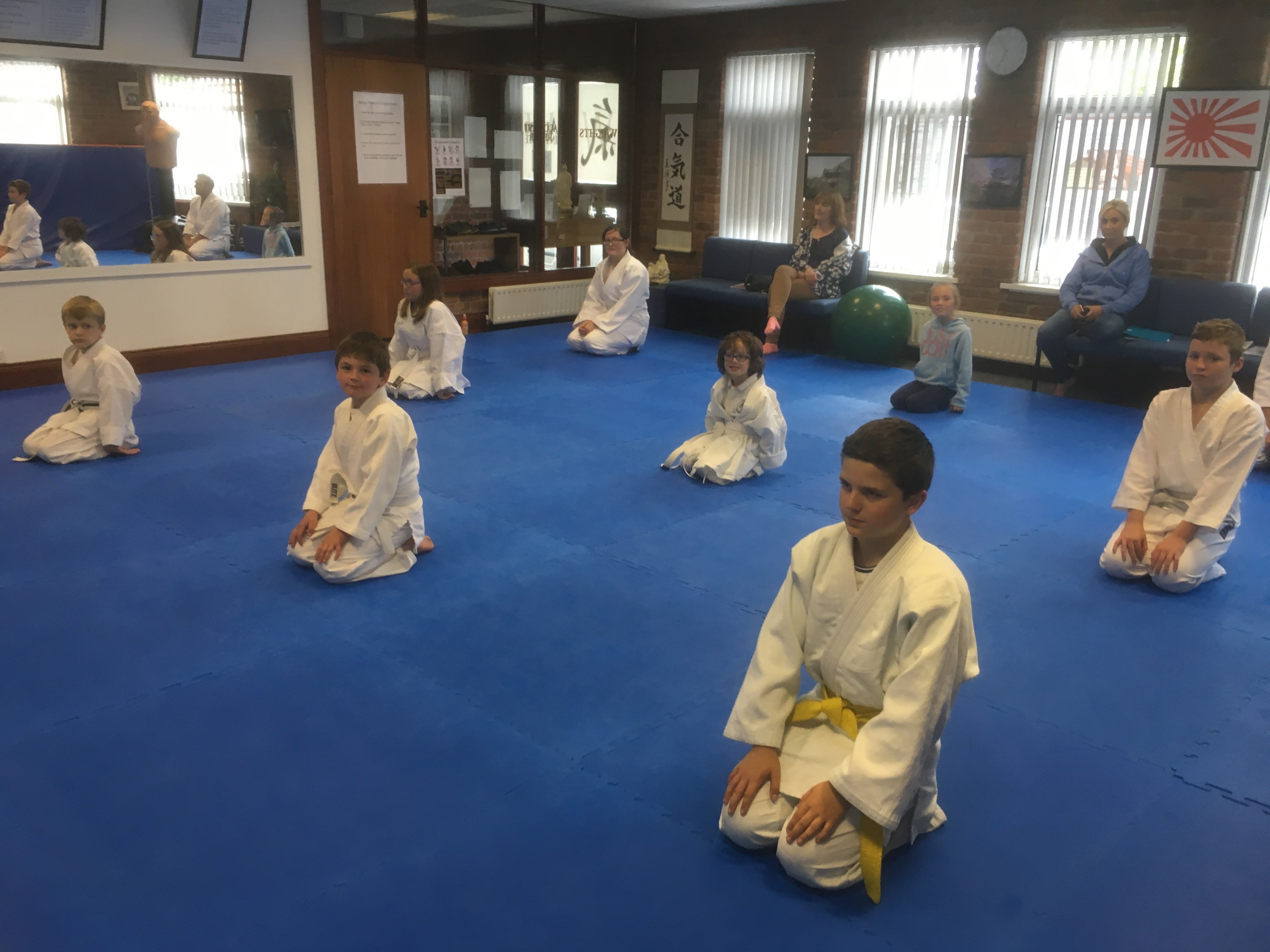 Class of aikido students kneeling on blue floor