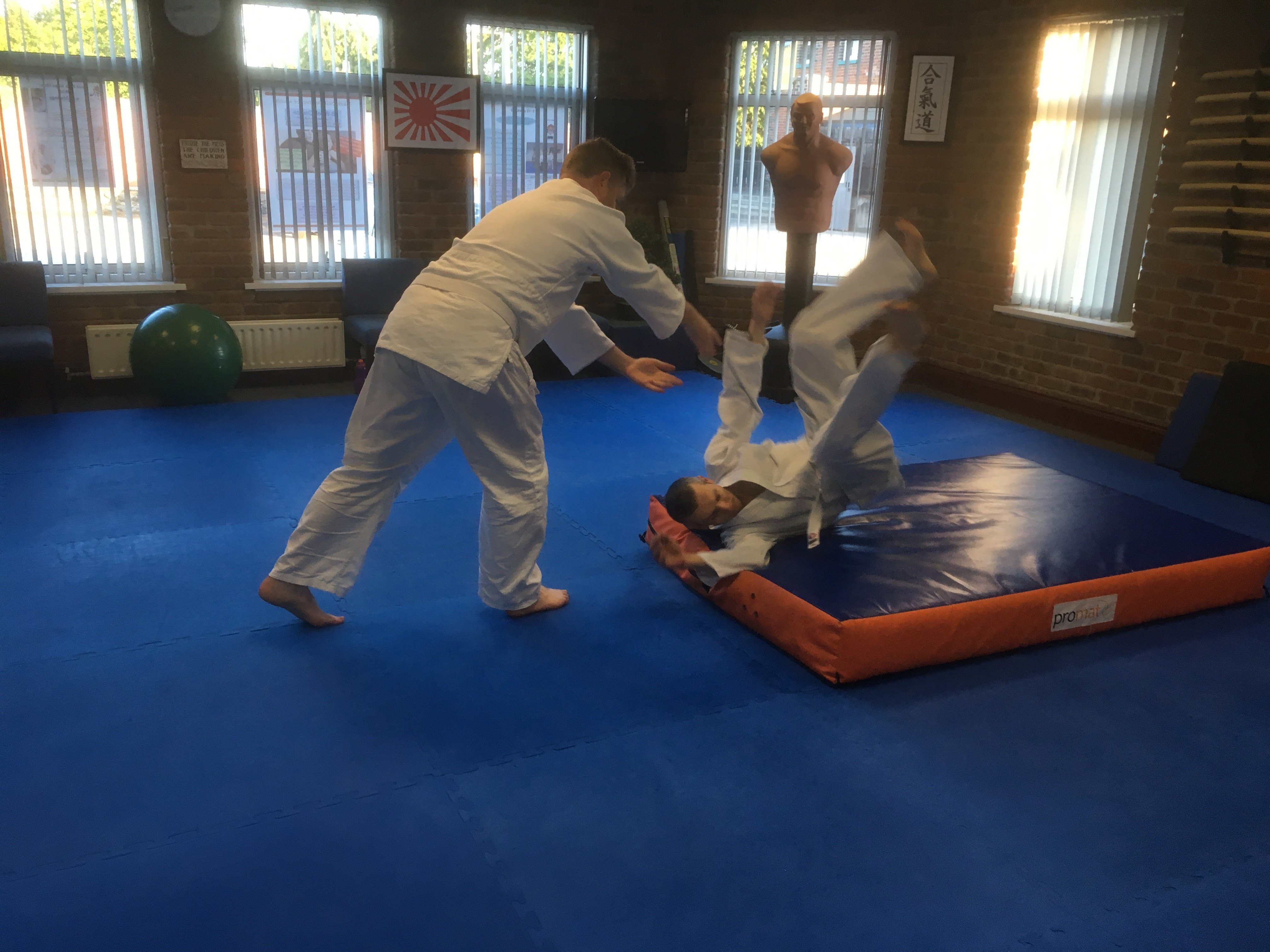 Two Aikido male students learning to fall safely on the crash mat. Martin Acton's Aikido Institute