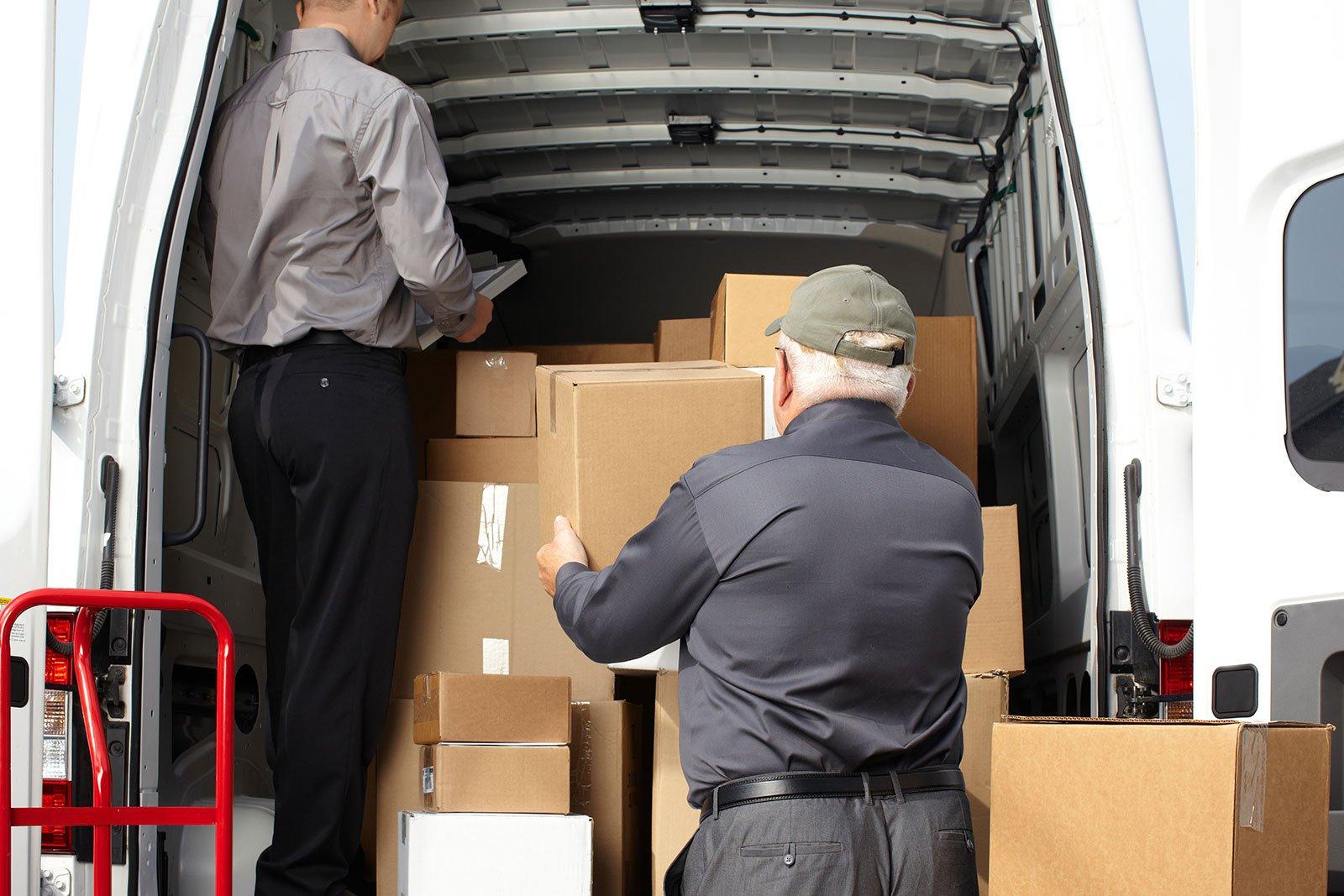 due uomini che scaricano degli scatoloni da un furgone