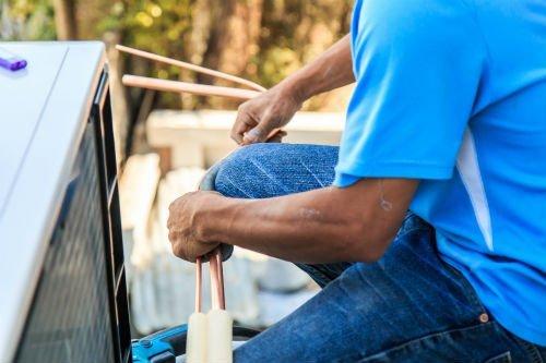 un operaio mentre ripara un condizionatore