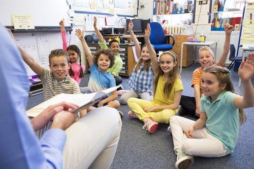 bambini seduti per terra con mani alzate