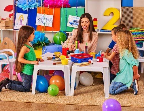 bambini e insegnante mentre fanno dei giochi costruttivi
