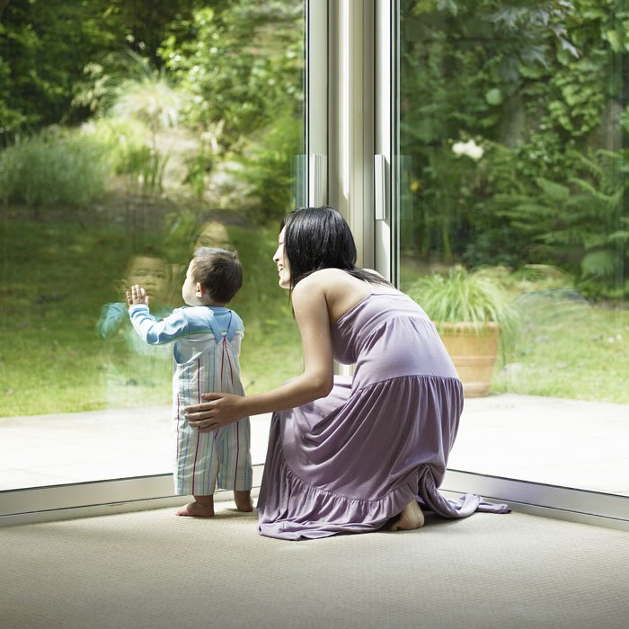 little boy and mother looking out window