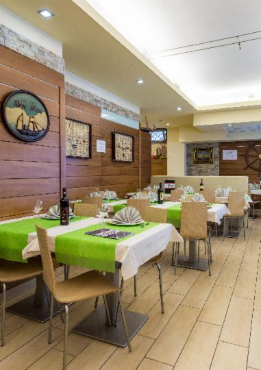 Interno del ristorante, pavimento di legno, anche mobili e parete. Tovaglie e tovaglioli  bianchi e verdi
