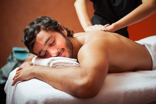 un ragazzo sdraiato e una donna che gli fa un massaggio