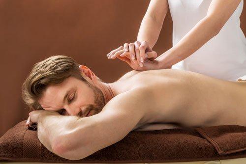 una donna che massaggia la schiena di un ragazzo sdraiato