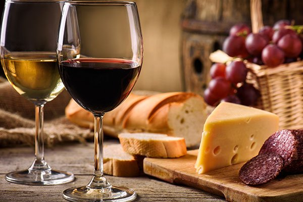 Pane, un paniere di pomodori, formaggio,salame e vino rosso e bianco per godere