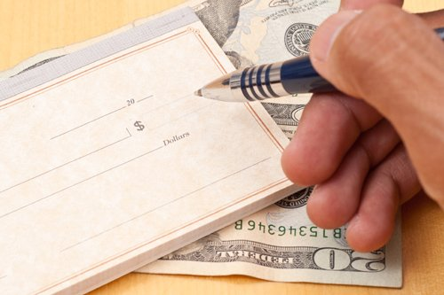Hand writing a check for cash advance in Omaha, NE