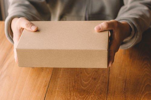 persona consegna un pacco in cartone