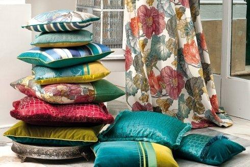 cuscini verdi e di diversi colori uno sopra l'altro e una tenda bianca a fiori rossi verdi e arancioni