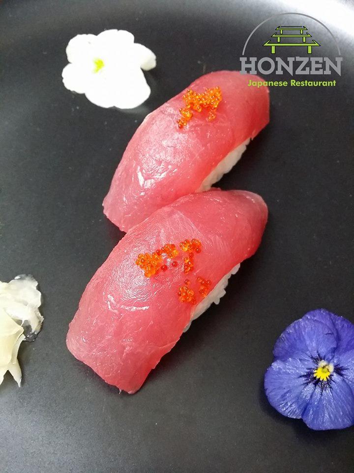 Un'immagine di un piatto con sushi al salmone, delle uova di salmone e una scritta Honzen Japanese restaurant
