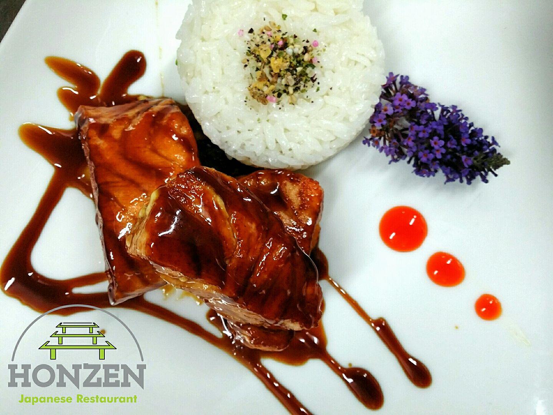Un piatto con riso bianco, aromi, filetto di pesce e decorazioni con fiori di color viola