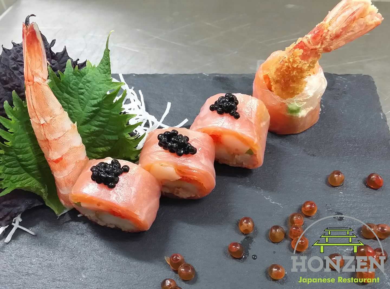 Un piatto con sushi, tempura e gamberoni