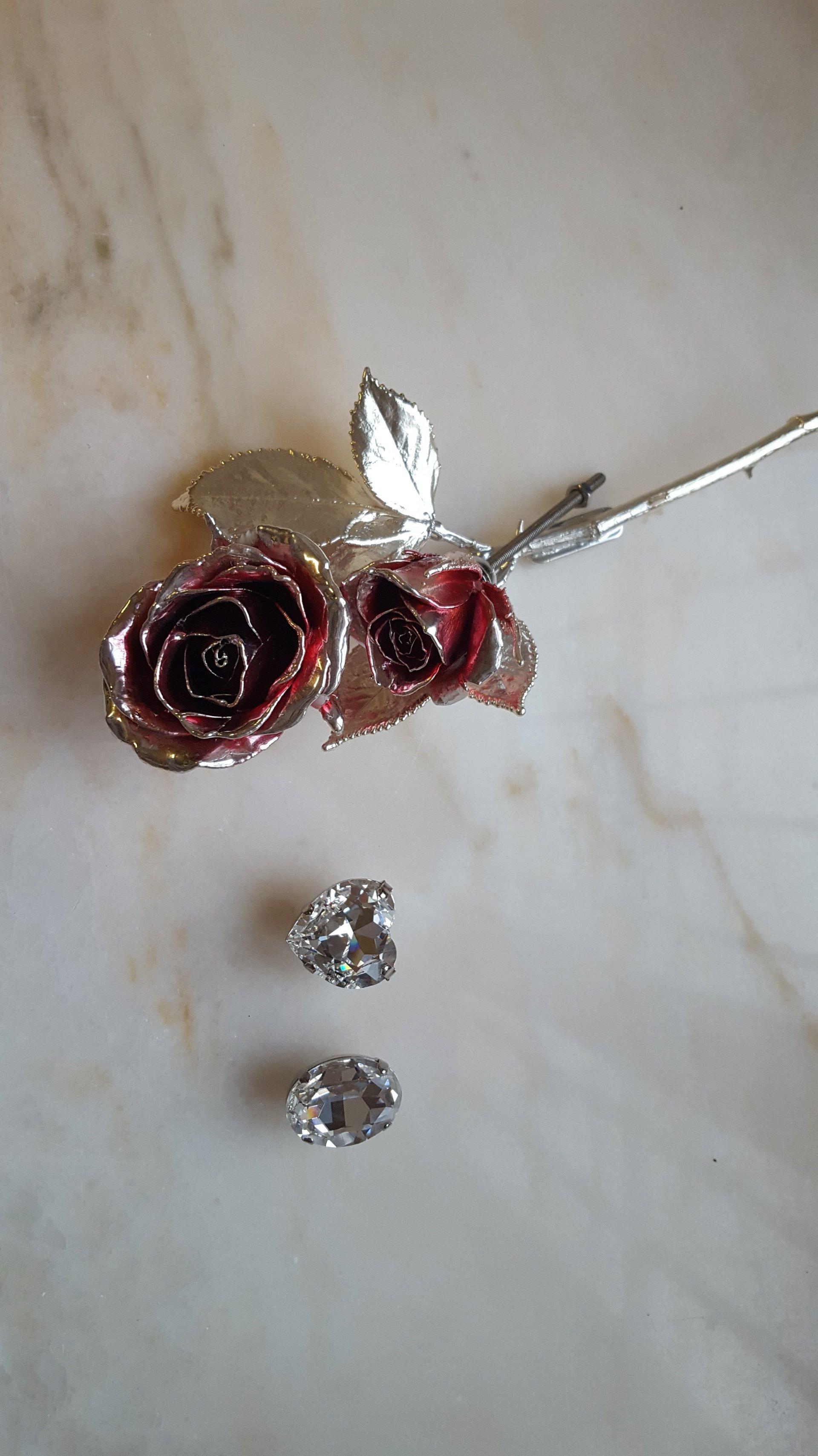 due rose rosse dorate e due cristalli