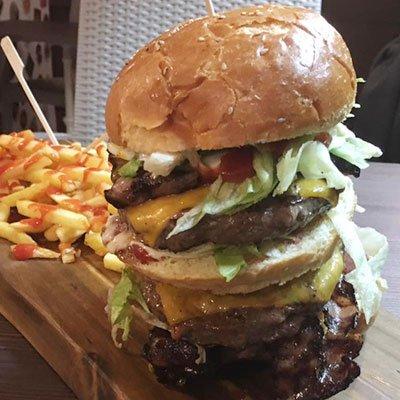 un hamburger con tanti strati e dietro delle patatine fritte con del ketchup