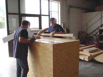 Due tecnici chiudono una cassa da imballaggio.