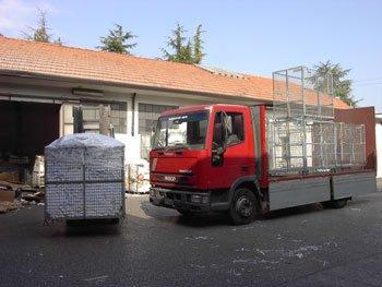 Camion rosso davanti a edificio industriale.