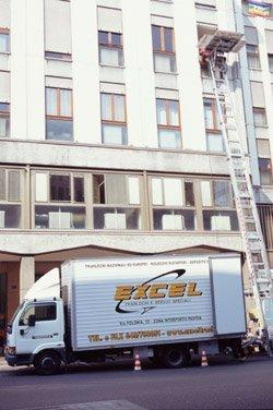 Fianco di un furgone per traslochi di fronte a un palazzo.