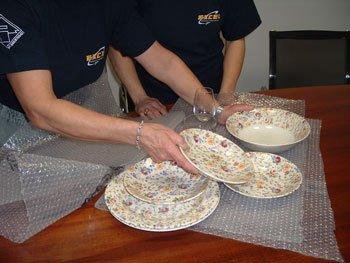 Addette che avvolgono piatti decorati e bicchieri da vino nel pluriball.
