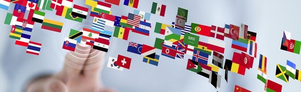 Mano premendo uno schermo con le bandiere di molti paesi