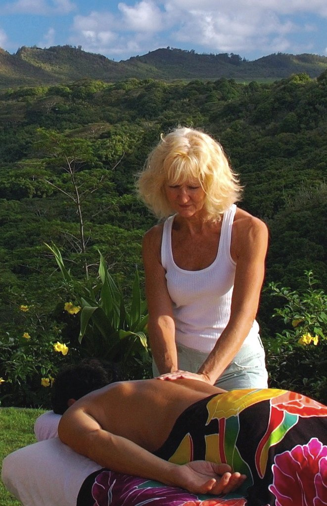 Manima at Mana Massage giving woman massage at Wailua River Valley in Kapaa, HI