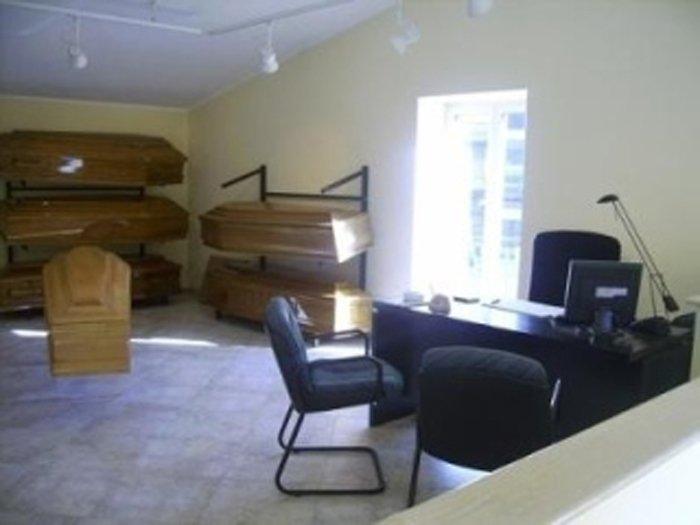 ufficio con cofani in legno, scrivania e poltrone