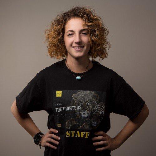 una ragazza con le mani sui fianchi e una t shirt con scritto The Fighters Staff