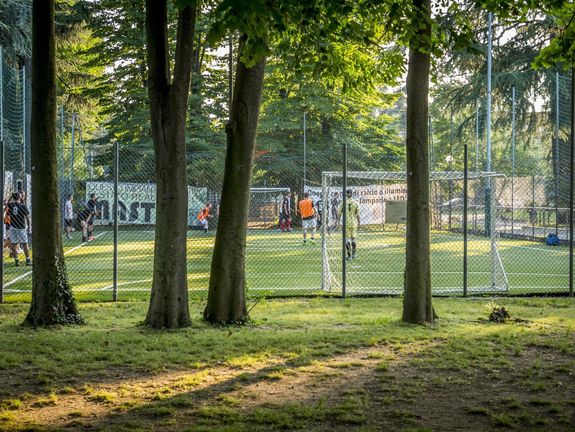 vista campi da calcio con persone che giocano e alberi