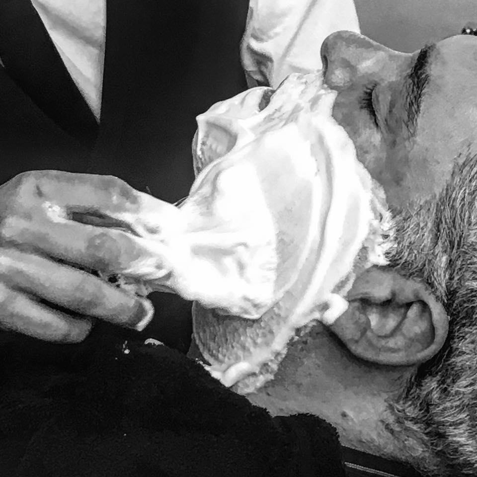 barbiere che mette la crema da barba a un cliente