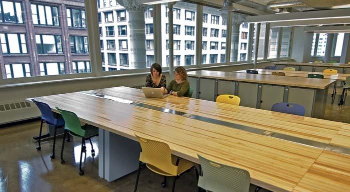 aula universitaria con due studenti, banchi in legno e sedie