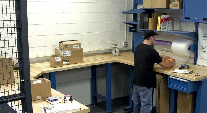 operaio lavora su bancone in metallo e legno