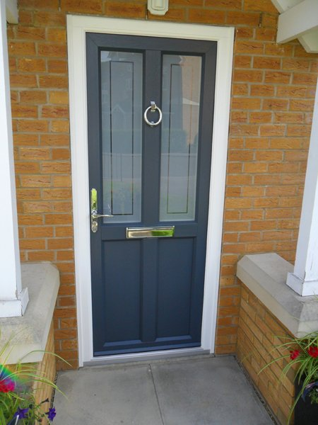 Grey front door made of timber replacement products