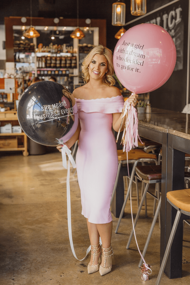 Women in a pink dress holding balloons