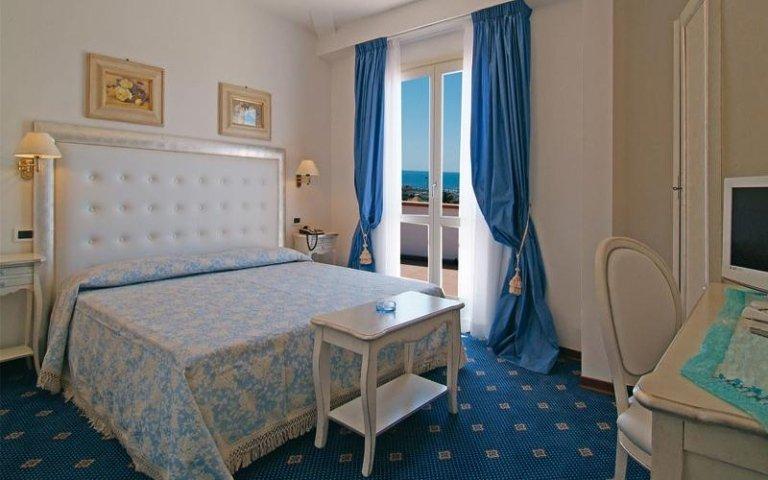 una camera d'albergo con un letto matrimoniale, un tavolino e una scrivania con sopra una tv