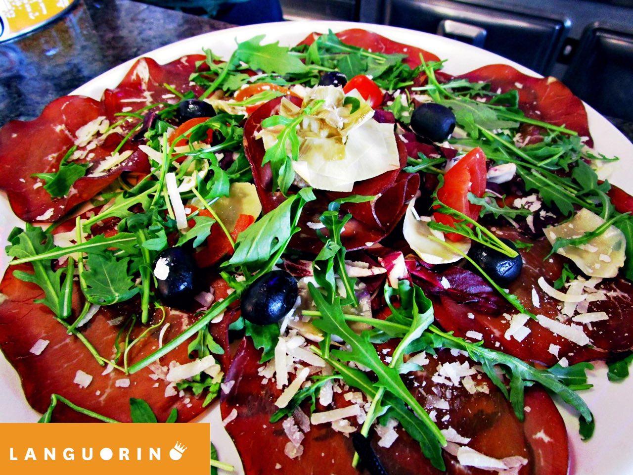 Piatto di prosciutto con pomodori freschi, rucola e parmigiano
