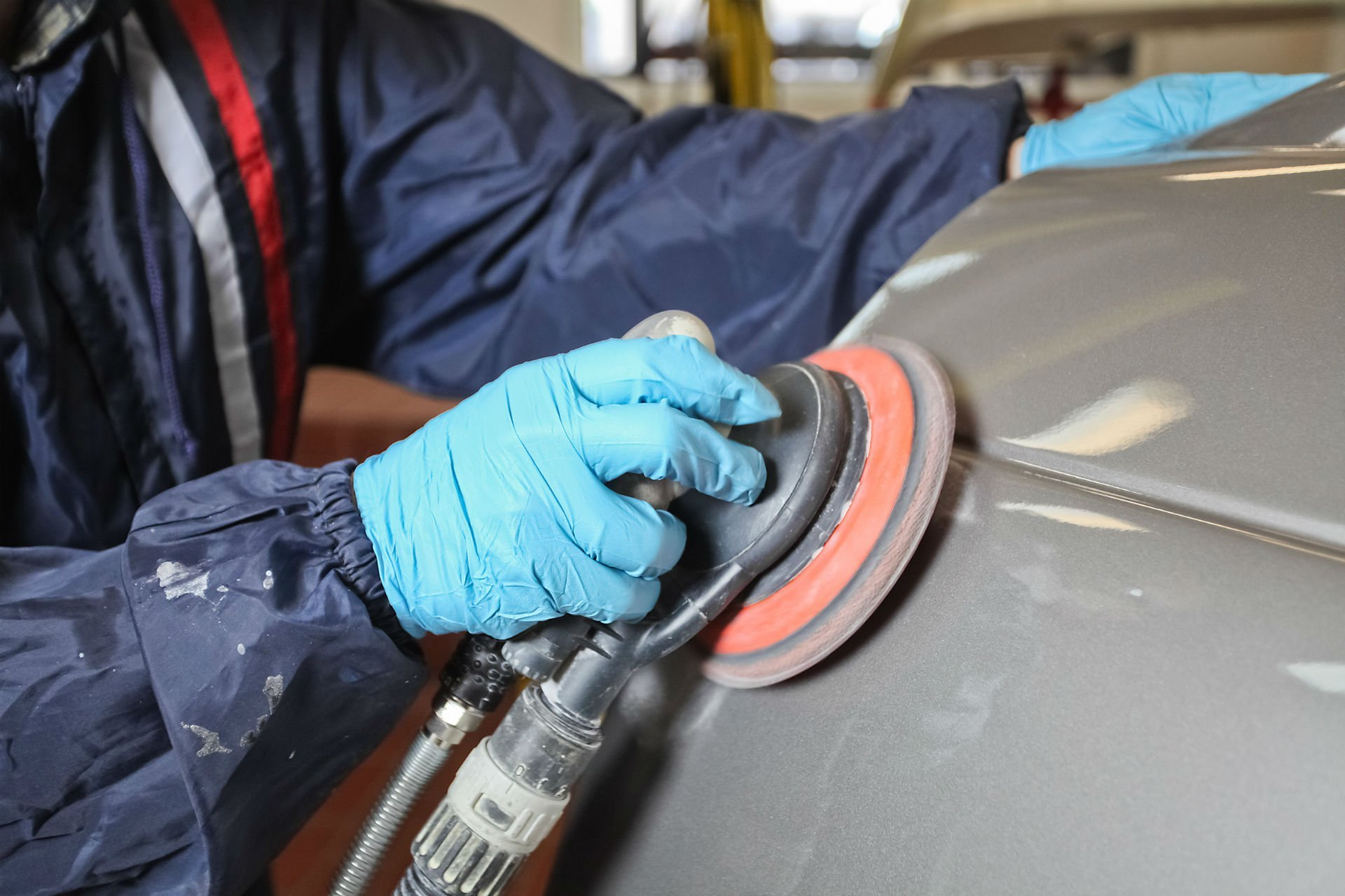 una mano con una lucidatrice appoggiata sulla carrozzeria di una macchina