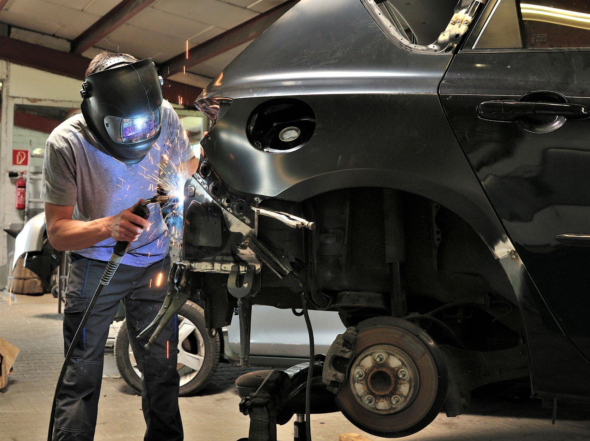 un carrozziere con una maschera durante un lavoro di saldatura