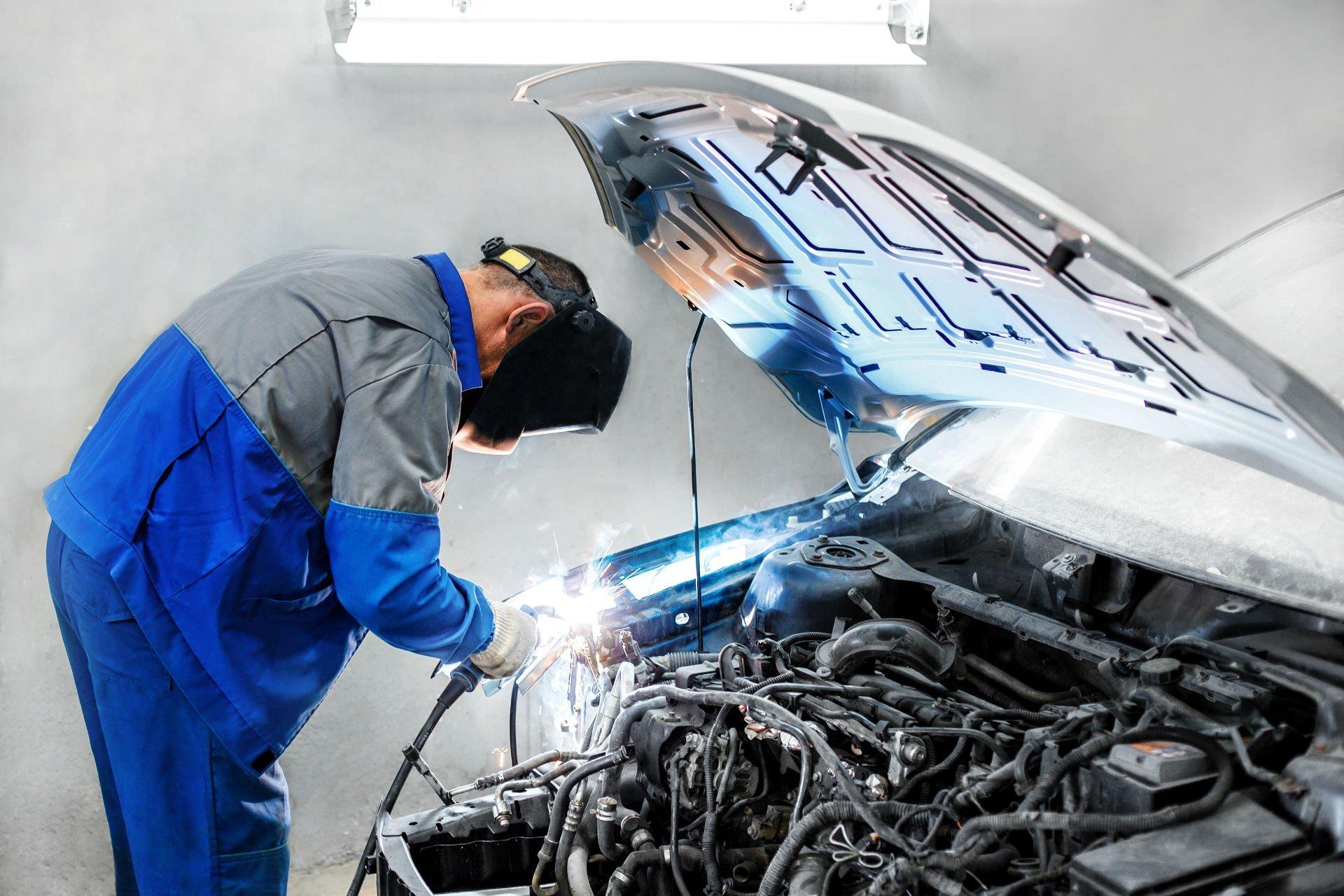 un carrozziere che salda dei componenti nella zona motore di una macchina