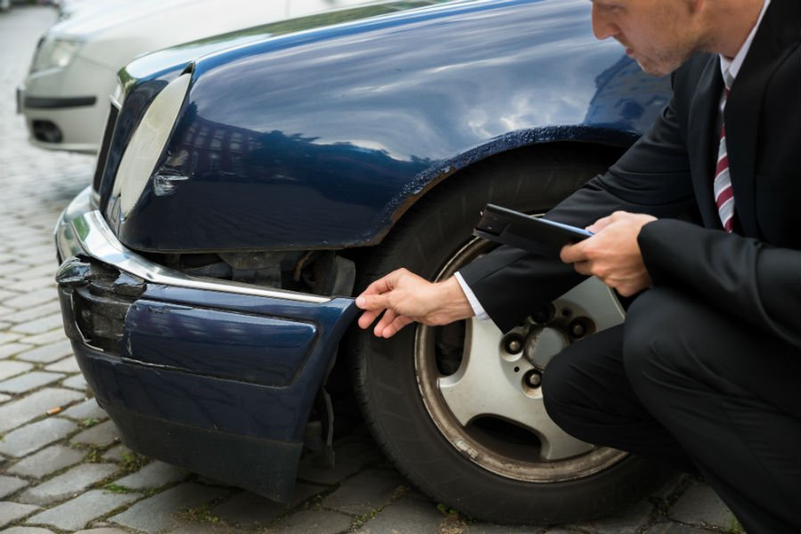 un uomo chinato a terra con un telefono in mano mentre controlla un danno alla parte anteriore della carrozzeria di una macchina