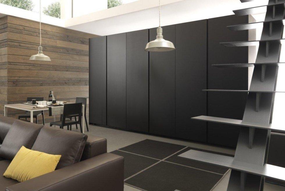 vista interna di una sala da pranzo con armdi neri, scala, divano, cuscini e parete in legno