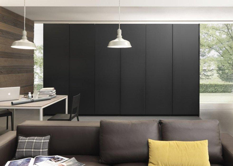 vista interna di una sala da pranzo con armdi, divano, cuscini e parete in legno