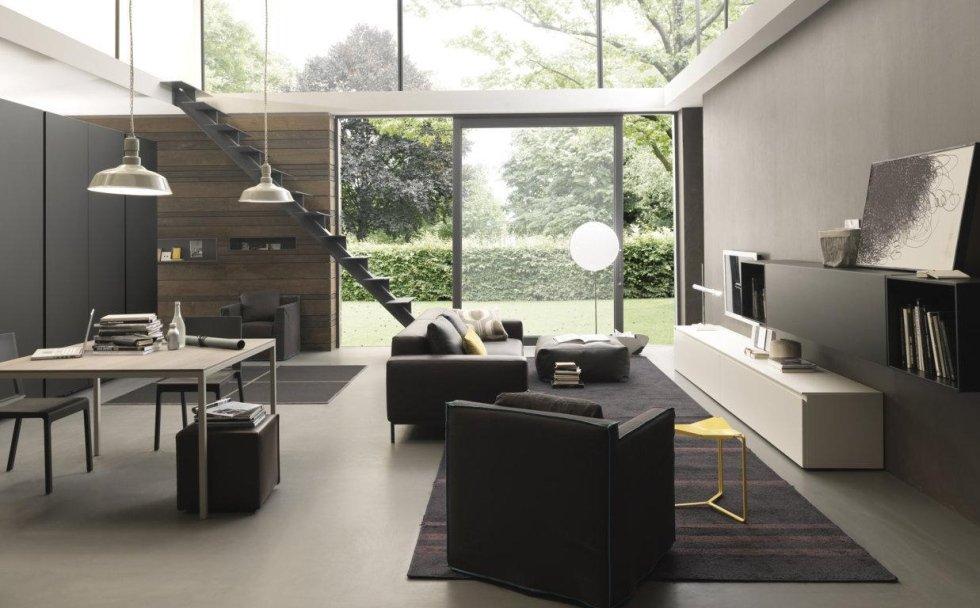 soggiorno con divano, poltrona, scala interna, tavolo e sedie e porta in vetro