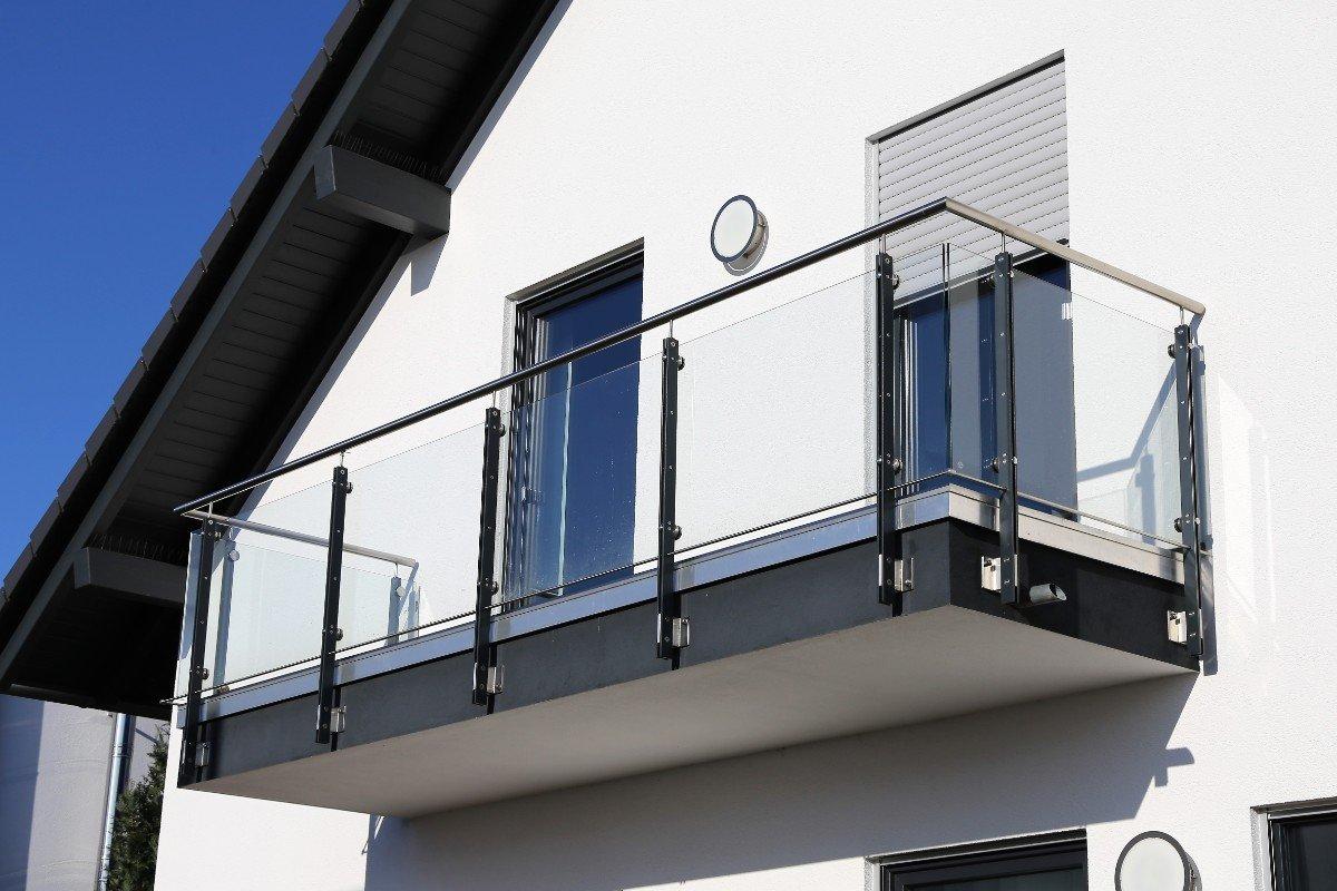 un balcone di una casa con parapetto in vetro