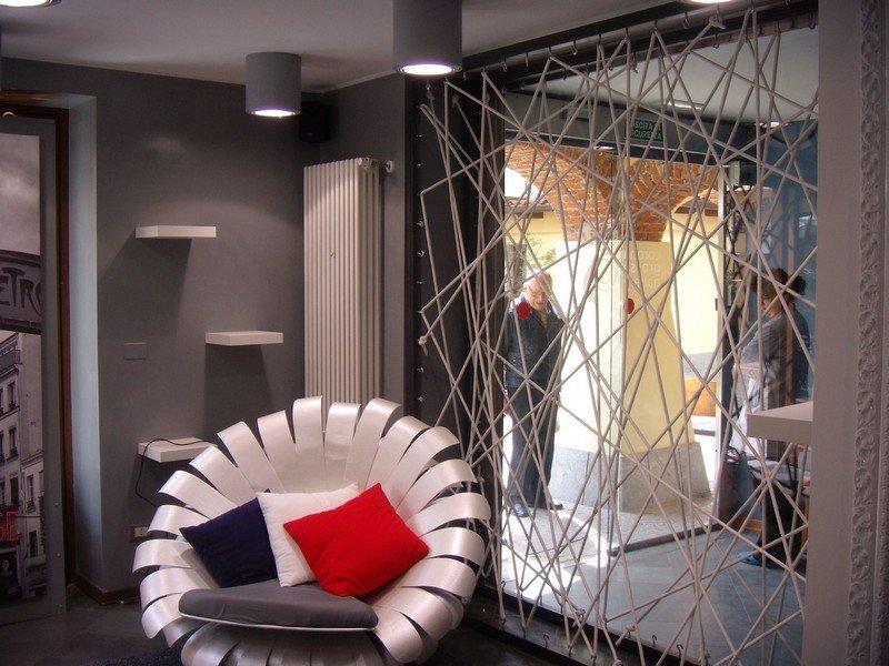 Faretti per l'illuminazione di uno studio arredato in stile moderno e con poltrona di design con cuscini rossi bianchi e blu