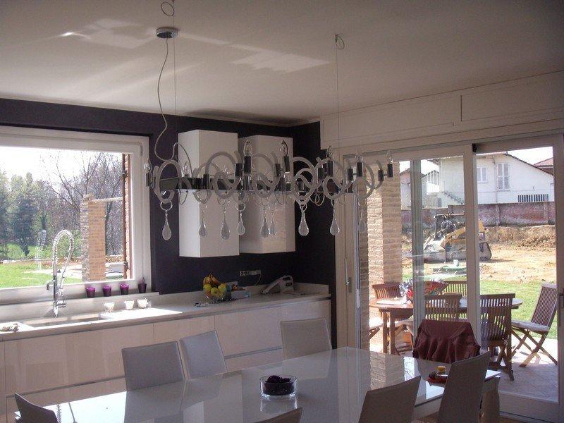 Lampadario di design in un'ampia cucina privata con grandi finestre